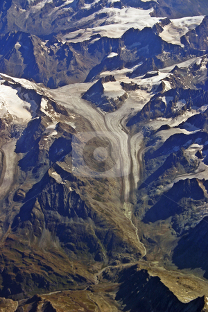 Aerial view of a glacier in the Alps vertical stock photo, Aerial view of a flowing glacier in the Swiss Alps during summer vertical by Stephen Goodwin