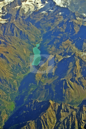 Aerial view of a mountain lake in Switzerland vertical stock photo, Aerial view of a mountain lake in the Swiss Alps during summer with  green valley and white glacier vertical by Stephen Goodwin