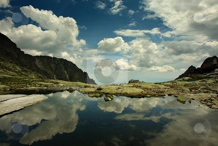 Mountain lake with gorgeous sky stock photo, Mountain lake with gorgeous cloudy sky and a cottage by Juraj Kovacik
