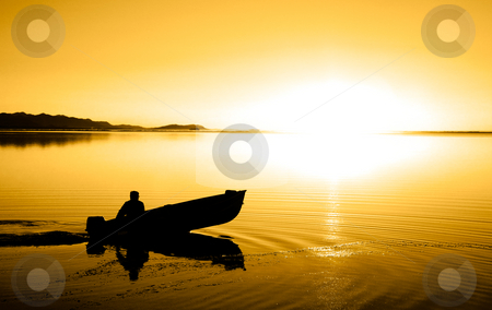 Pacific Northwest Sunset stock photo, A man in a boat at Cline Spit in Sequim Washington. by Travis Manley