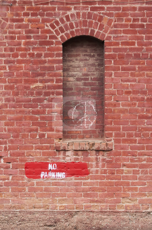 No Parking stock photo, Brick wall with no parking and peace signs by Scott Griessel