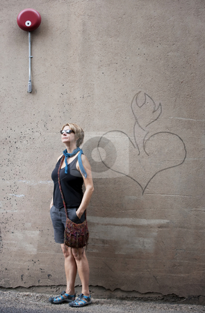 Tourist stock photo, Female tourist in front of cement wall with heart drawing by Scott Griessel