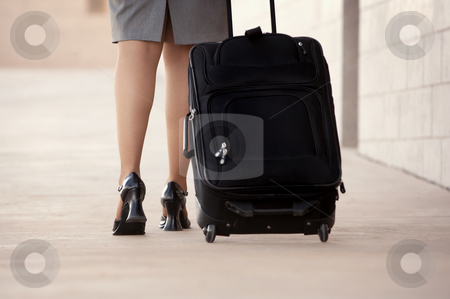 Woman with roller bag stock photo, Close up of woman's legs and feet with roller suitcase by Scott Griessel