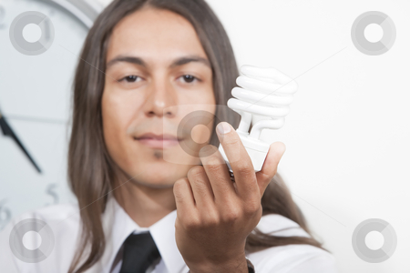 Man with energy efficient lightbulb stock photo, Handsome young man holding energy efficient lightbulb by Scott Griessel