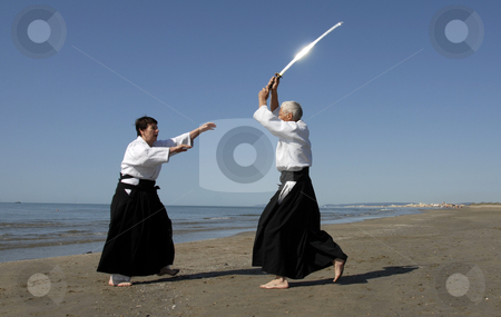Aikido on the beach stock photo, Two adults are training in Aikido on the beach by Bonzami Emmanuelle