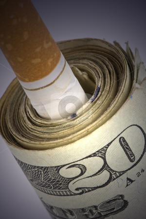 Cigarette in money roll stock photo, Cigarette stuck in roll of money close up by Chris Roselli