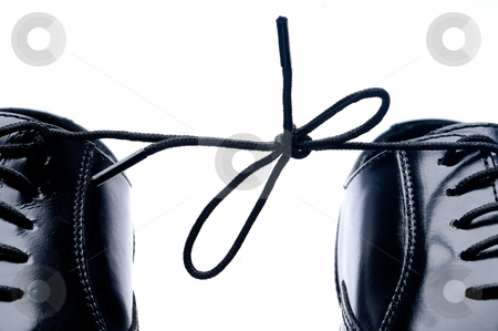Horizontal close up of a pair of black leather business shoes wi stock photo, Horizontal close up of a pair of black leather business shoes with laces tied together by Vince Clements