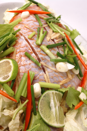 Steamed fish stock photo, Whole fresh fish prepared for steaming, with fresh ingredients on top for flavour. High key with shallow depth of field by Martin Darley