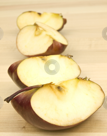 Sliced apples in a row stock photo, Sliced apples in a row on a wooden background by John Teeter