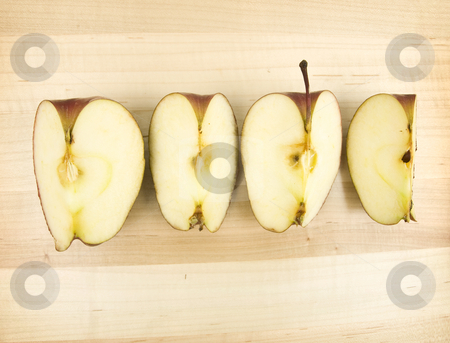 Sliced apple four ways stock photo, Sliced apple on a wooden background by John Teeter