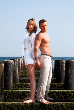 Man and woman back to back stock photo, Beautiful sexy fashion couple standing back to back holding hands on a wooden pier covered with algea going into the ocean water on a summer day with blue skies. by Paul Hakimata