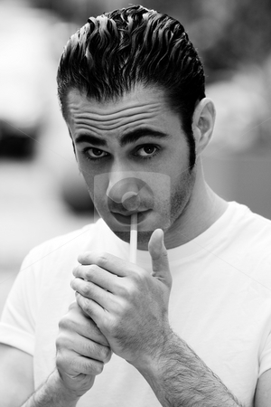 Man lighting cigarette stock photo, Handsome Caucasian man wearing white shirt lighting a filter cigarette, on a blurred outdoor background by Paul Hakimata