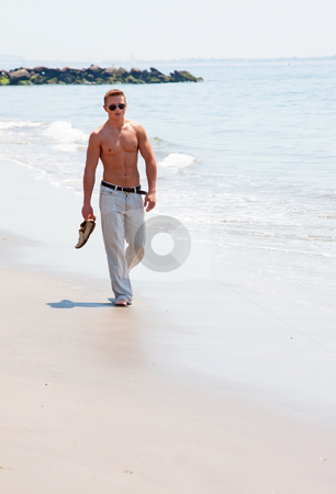 Handsome man walking on beach stock photo, Toned cute handsome male walking on the beach with naked torso showing six pack abs holding shoes in hand wearing sunglasses by Paul Hakimata