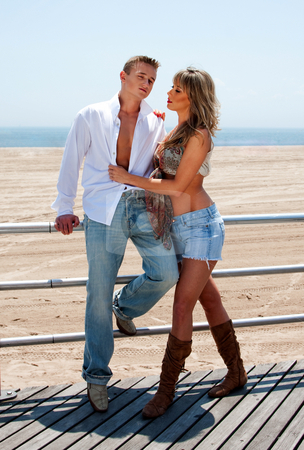 Sexy fashion couple stock photo, Young sexy couple, man and woman, next to railing on the boardwalk at the beach standing romantically together by Paul Hakimata