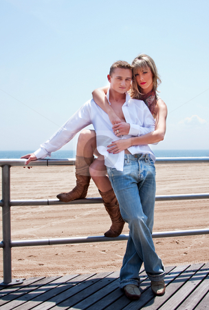 Sexy romantic couple stock photo, Young romantic sexy couple, man and woman, next to railing on the boardwalk at the beach standing together with her arms him by Paul Hakimata