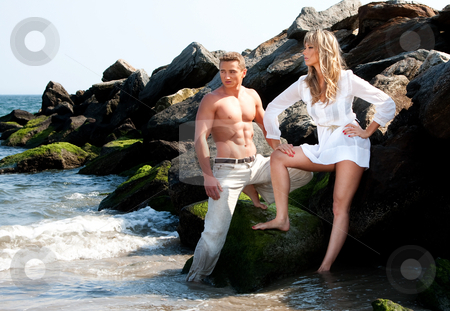 Fashion models at beach stock photo, Caucasian guy and girl together on rock formation next to ocean water. Female is wearing long white shirt. Both standing on rocks at the beach. Guy showing muscular abs and bare torso wearing beige pants, heaving cool attitude. Together hanging out. by Paul Hakimata