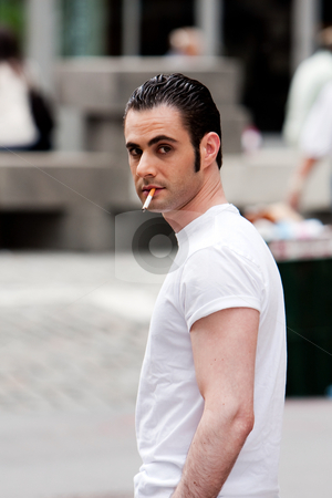 Surveillance photo of man stock photo, Secret surveillance photo of a Caucasian mafia man with cigarette dressed in white t-shirt on the street by Paul Hakimata