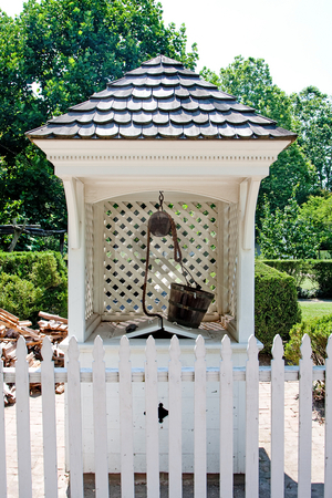 Water well stock photo, A white wishing water well in Colonial style with wooden bucket on top and roof with shingles behind a white picket fence in a garden. by Paul Hakimata