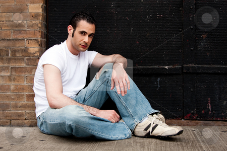 Man sitting on concrete stock photo, Handsome Caucasian man with sideburns dressed in white shirt and blue jeans sitting on concrete floor in front of black metal garage door by Paul Hakimata