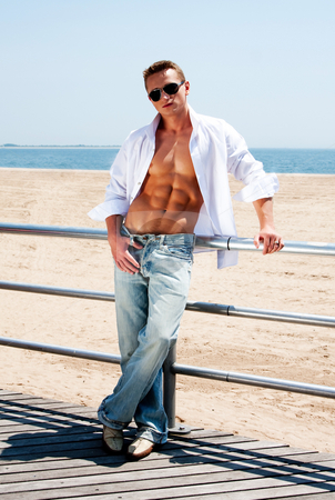 Sexy man at beach stock photo, Sexy handsome male with sunglasses and toned body showing six pack abs with white shirt opne while standing next to railing on boardwalk at beach by Paul Hakimata