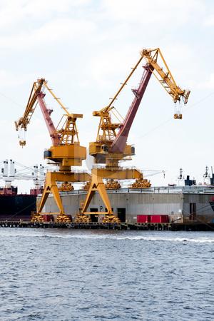 Heavy duty port crane stock photo, Heavy duty yellow cranes on rails for loading cargo onto ships at a port terminal by Paul Hakimata