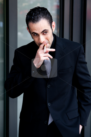 Business man smoking stock photo, Secret surveillance photo of a Caucasian mafia business man smoking a cigarette dressed in a black suit by Paul Hakimata