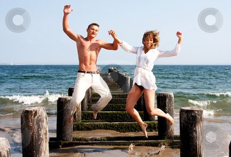 Happy couple jumping stock photo, Cute happy couple smiling jumping playfully at the beach with a pier and the ocean water in the background heaving fun by Paul Hakimata