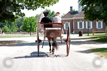 Colonial horse carriage with couple stock photo, Rear view of a historical couple of a man and a woman dressed in Colonial American style on a brown carriage with treasure chest pulled by a horse in Colonial Williamsburg, Virginia by Paul Hakimata