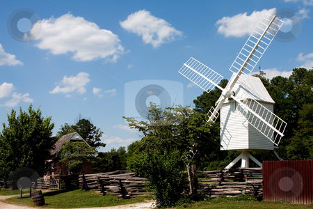 White windmill stock photo, A white wooden windmill in a small meadow behind a wooden fence on a summer day with blue skies surrounded by trees in Colonial Williamsburg, Virginia. by Paul Hakimata