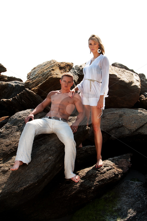 Fashion couple stock photo, Caucasian guy and girl together on rock formation. Female is wearing long white shirt and holding sunglasses, standing on rocks. Guy showing muscular abs and bare torso wearing beige pants, heaving cool attitude, sitting on rocks. Together hanging out. by Paul Hakimata