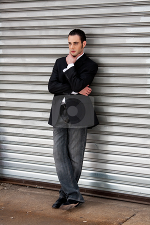 Business man standing stock photo, Handsome casual business man standing in front of and leaning against silver metal garage door with hand on chin thinking by Paul Hakimata
