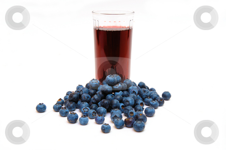 Blueberries And Blueberry Juice stock photo, Blueberries are a good source of antioxidants. a clear  glass with berry juice with berries all around on a white background. by Lynn Bendickson
