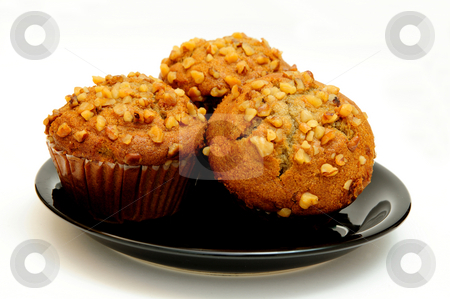 Banana Muffin stock photo, Closeup of three banana nut muffins topped with crushed walnuts on a black saucer with a light colored background. by Lynn Bendickson
