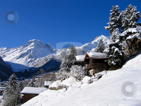 Chalets in a snow white valley stock photo, Chalets in a snow white valley in the Swiss Alps on a clear day. by Peter Van veldhoven