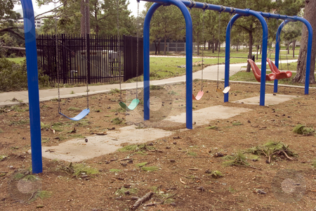 Swings stock photo, Swings at a abandoned playground around pine trees by Kevin Tietz