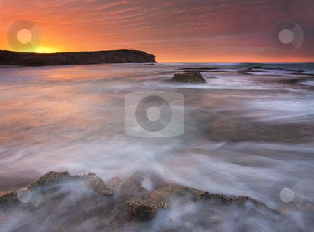 Splitting the Tides stock photo, A rock shelf splitting the incoming tides as the sun rises on Pennington Bay South Australia. by Mike Dawson
