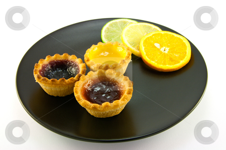 Jam Tarts with Citrus Slices stock photo, Red and yellow small jam tarts with slices of lemon, lime, and orange on a black plate on a white background by Keith Wilson