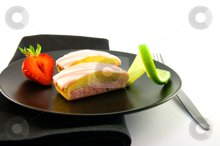 Strawberry Slices with Strawberry and Lime stock photo, Two pink strawberry sliced cakes with icing on the top with a half strawberry and twist of lime on a black plate with a black napkin and fork on a white background by Keith Wilson
