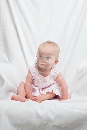 Pink Dress stock photo, Cute little caucasian baby girl wearing pink dress on a white background by Mariusz Jurgielewicz