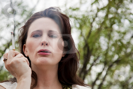 Woman Smoking stock photo, Woman smoking cigarette outdoors with tree in background by Scott Griessel