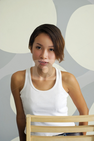 Young Sexy Asian Woman stock photo, A young and sexy Asian woman sitting on a chair and posing in front of a grey bubble background. Adobe RGB color profile. by Stefan Breton