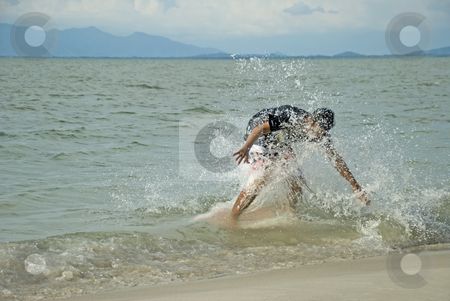 Skin boarder in a wave stock photo, A young man skin boarding at the beach on a sunny day. by Stefan Breton
