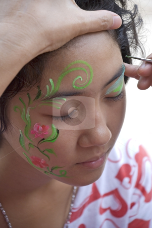 Painted face girl stock photo, A young girl getting her face hand painted. by Stefan Breton