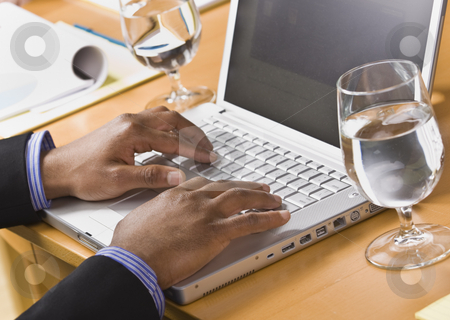 African American male hands on laptop. stock photo, African American male hands typing on laptop keyboard. Glass of water on desk. Horizontal by Jonathan Ross