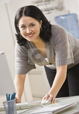 Woman on Computer stock photo, A businesswoman is standing over a computer and smiling at the camera.  Vertically framed shot. by Jonathan Ross