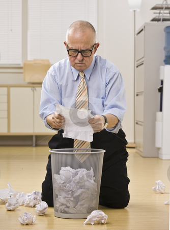 Senior male reading paper at garbage. stock photo, Senior male kneeling on floor reading paper at garbage. Vertical. by Jonathan Ross