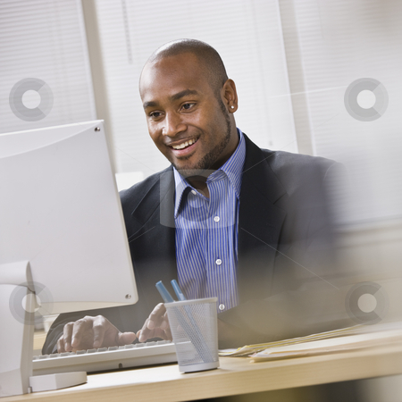 Attractive African American at computer. stock photo, Attractive African American smiling at computer, while sitting at a desk typing on keyboard. Square. by Jonathan Ross
