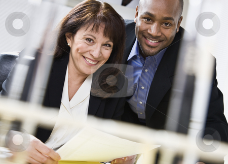 Attractive couple reading paper. stock photo, Attractive couple reading paper. Male above female, in business suits. Horizontal. by Jonathan Ross