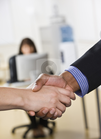 Man and Woman Shaking Hands stock photo, A businessman and woman are shaking hands in an office. There is another woman working on a computer in the background Vertically framed shot. by Jonathan Ross