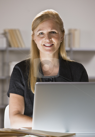 Woman on Computer stock photo, A businesswoman is sitting at a desk in an office.  She is working on a computer and smiling at the camera.  Vertically framed shot. by Jonathan Ross